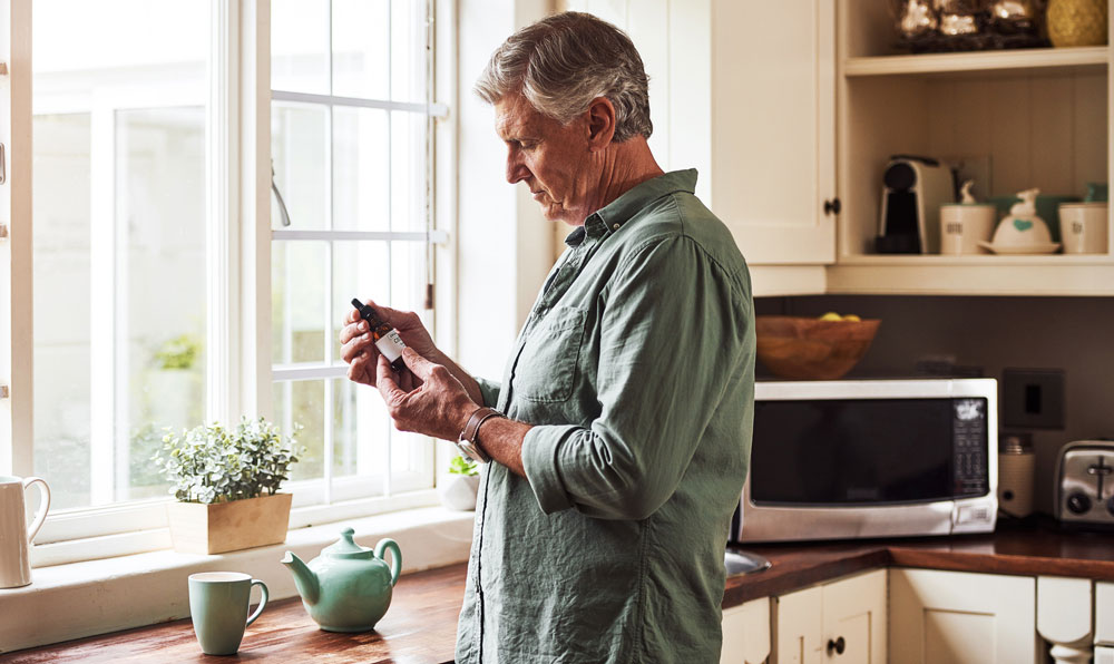 Senior man checking CBD oil label